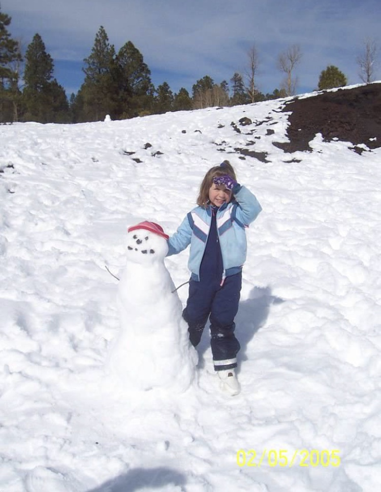 Marley Oakes standing next to a snowman outside Flagstaff, Arizona.